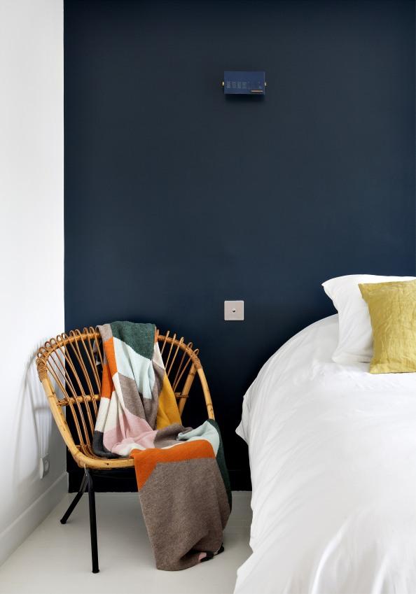 siege-vintage-en-bois-a-cote-d-un-lit-le-mur-derriere-le-lit-est-de-couleur-bleue-electrique-sizel-158111-1200-849