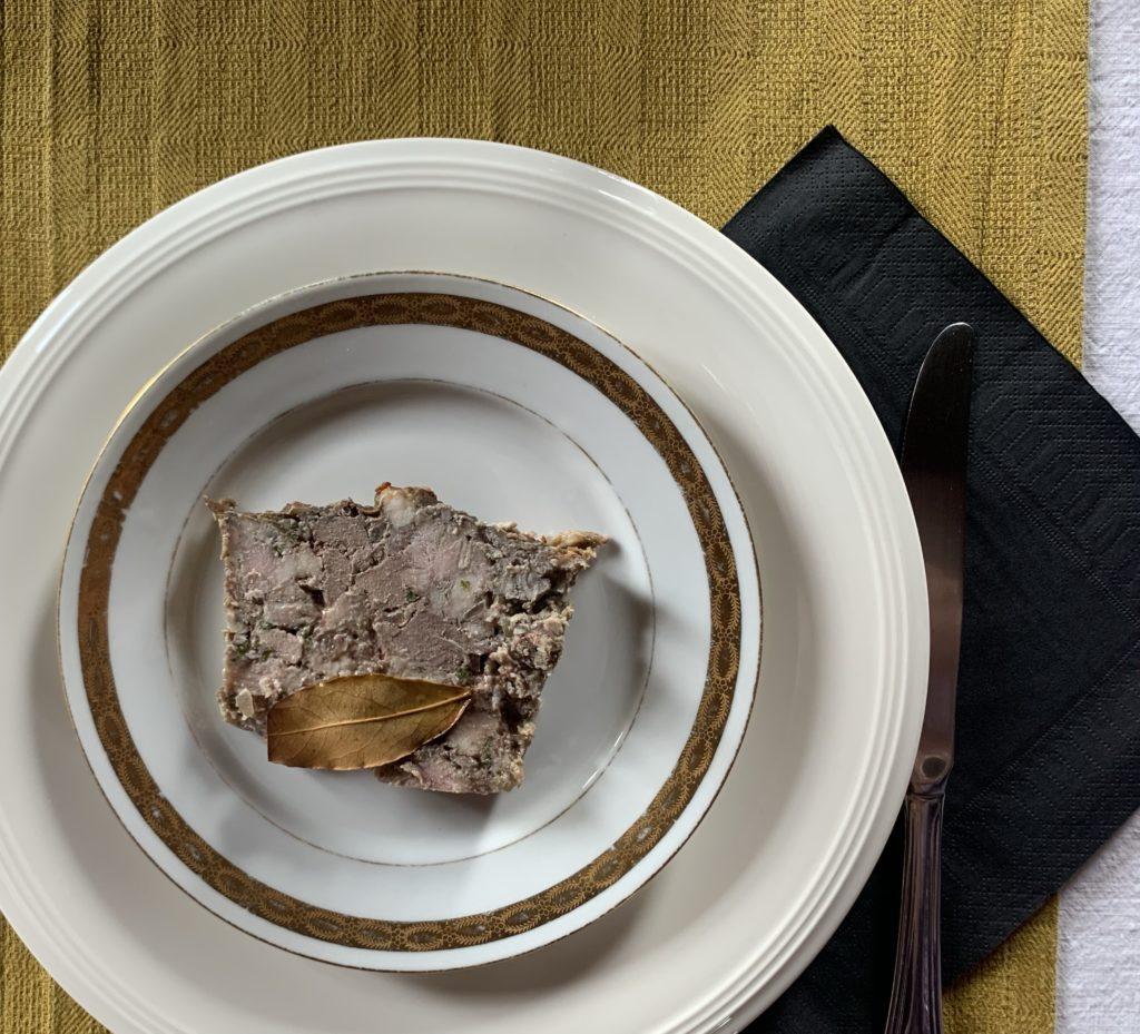 Tranche de pâté breton dans une assiette aux bords dorés